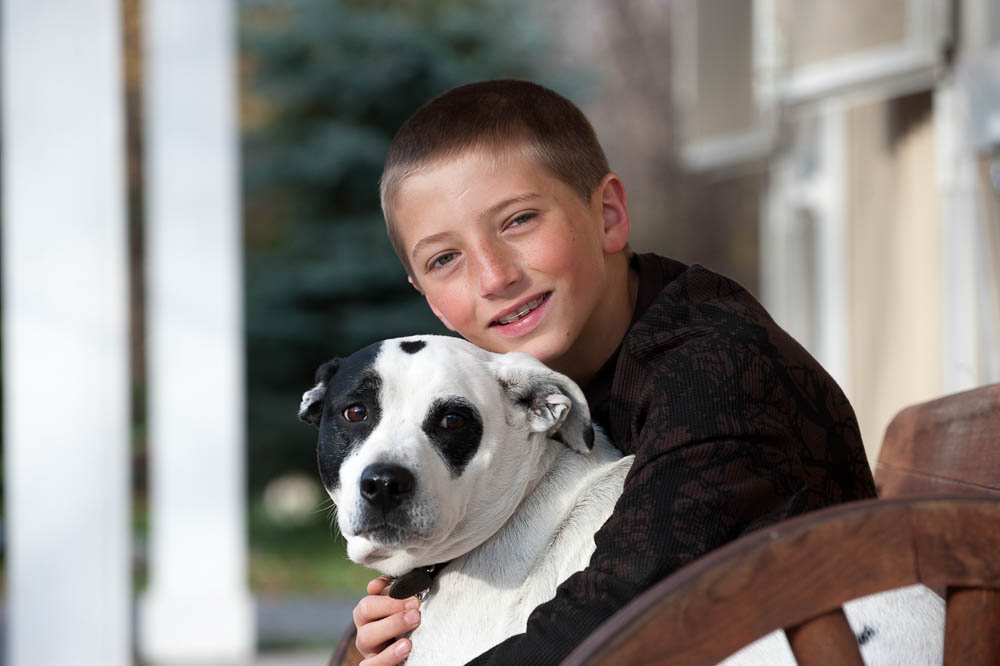 young boy photographed outside his home with his pet dog.